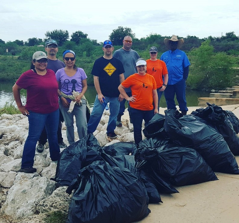 River Warriors cleaning up trash on the Mission Reach of the San Antonio River Walk following a storm event.