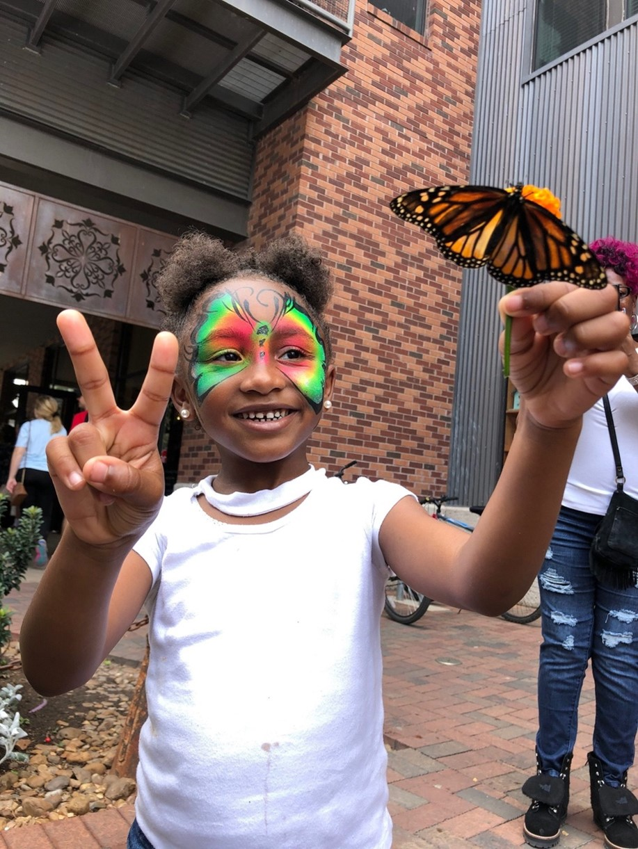 Participant holds monarch butterfly at the Monarch Butterfly and Pollinator Festival