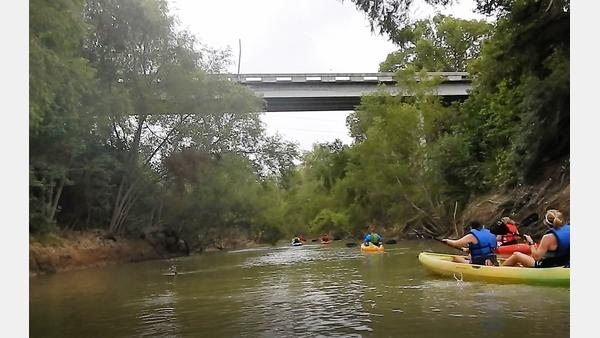 Paddling under a bridge along the SASPAMCO Paddling Trail