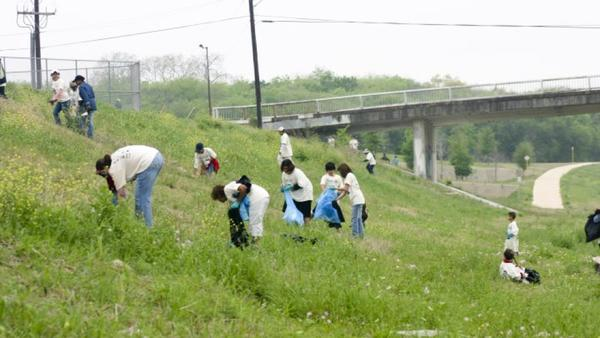 River Authority volunteers picking up trash along the San Antonio River.