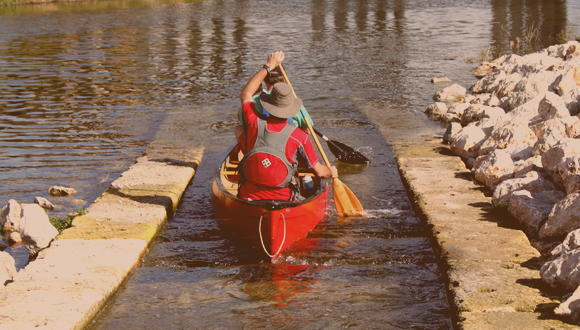 Two men paddling the San Antonio River in a canoe
