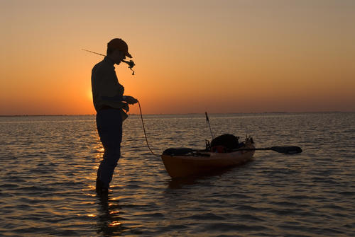 Silhouette of a man fishing in San Antonio Bay at sunset