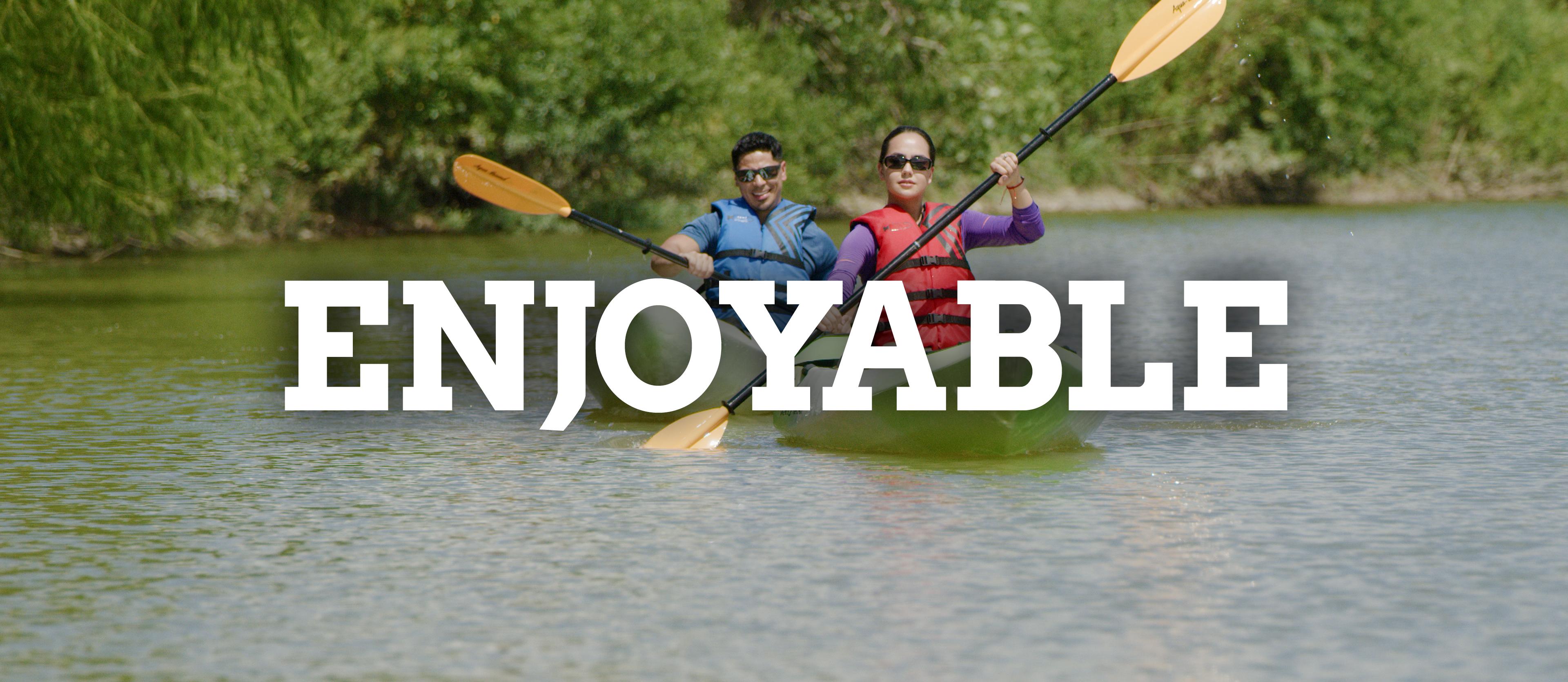 A man and woman kayak on the San Antonio River.