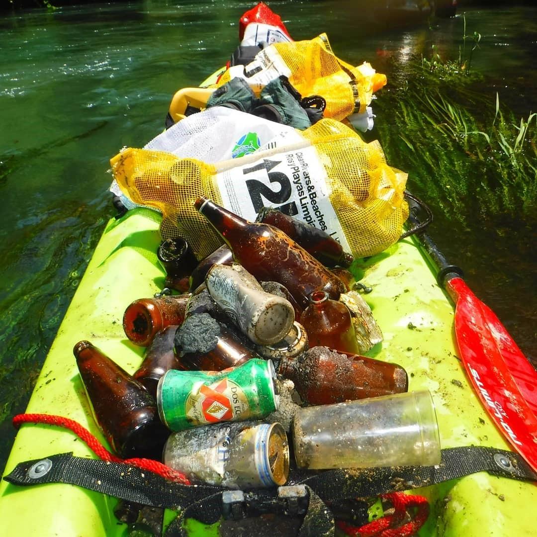 David Zambrano picks up trash in his kayak.